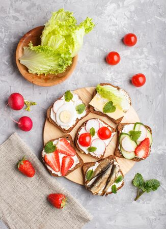 Set of different sandwiches with cheese, radish, lettuce, strawberry, sprats, tomatoes and cucumber on wooden board on a gray concrete background. top view, flat lay.