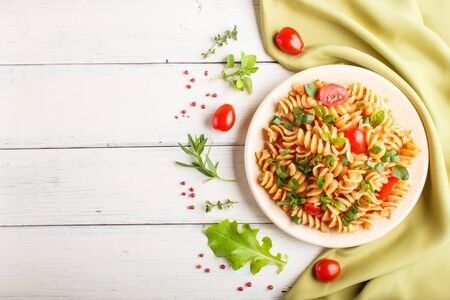 Fusilli pasta with tomato sauce, cherry tomatoes, lettuce and herbs on a white wooden background with green textile. top view, flat lay, copy space.