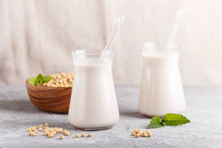 Organic non dairy soy milk in glass and wooden plate with soybeans on a gray concrete background. Vegan healthy food concept, close up, side view.