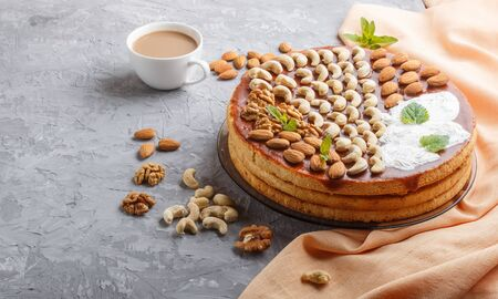 Homemade cake with caramel cream and nuts with cup of coffee on a gray concrete  background. side view, copy space.