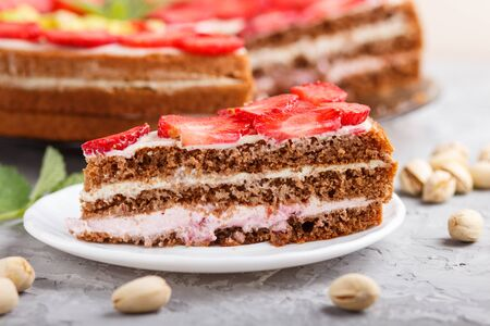 Homemade cake with yoghurt cream, strawberry, pistachio and a cup of coffee on a gray concrete  background. side view, selective focus, close up. Reklamní fotografie