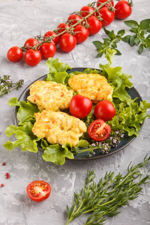 minced chicken cutlets with lettuce, tomatoes and herbs on a gray concrete background. side view, close up.
