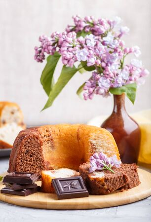 Cakes with raisins and chocolate and a cup of coffee. lilac flowers on a gray concrete background, side view. Reklamní fotografie