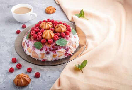 Homemade jelly cake with milk, cookies and raspberry on a gray concrete  background with cup of coffee and orange textile. side view. copy space.