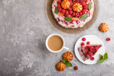 Homemade jelly cake with milk, cookies and raspberry on a gray concrete  background with cup of coffee. top view. flat lay, copy space.