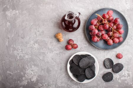 Black potato chips with charcoal, balsamic vinegar in glass, red grapes on a blue ceramic plate on a gray concrete background. Top view, flat lay, copy space.