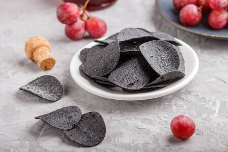 Black potato chips with charcoal, balsamic vinegar in glass, red grapes on a blue ceramic plate on a gray concrete background. side view, close up, selective focus. Reklamní fotografie