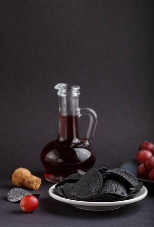Black potato chips with charcoal, balsamic vinegar in glass, red grapes on a blue ceramic plate on a black background. side view, close up, selective focus, copy space. Reklamní fotografie