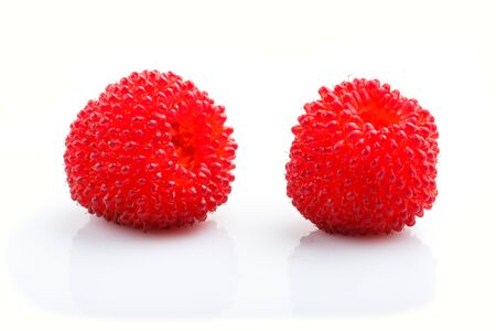 Two ripe red tibetian raspberry isolated on white background. side view, close up.