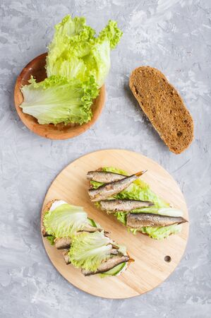 Sprats sandwiches with lettuce and cream cheese on wooden board on a gray concrete background. top view, flat lay.