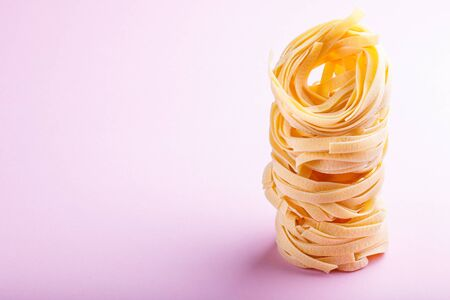 Raw uncooked tagliatelle pasta on a pink pastel background. side view, close up, copy space.