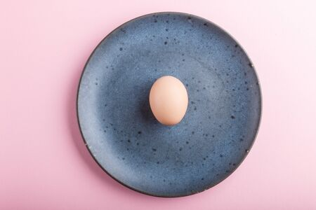 Raw uncooked single egg on a blue ceramic plate on a pink pastel background. top view, copy space.