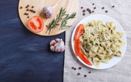 Farfalle pasta with pesto sauce, tomatoes and cheese on a linen tablecloth on black wooden background. top view, copy space.