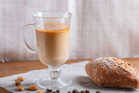Glass cup of coffee with cream  and bun on a wooden  background and linen textile. close up, copy space.