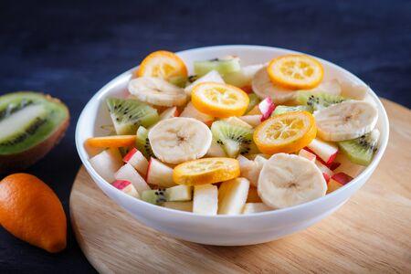 Vegetarian salad of bananas, apples, pears, kumquats and kiwi on black woodem background, close up, selective focus.