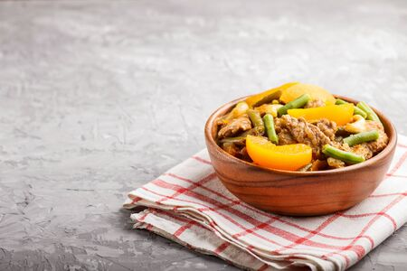 Fried pork with peaches, cashew and green beans in a wooden bowl on a gray concrete background. Side view, close up, copy space, chinese cuisine.