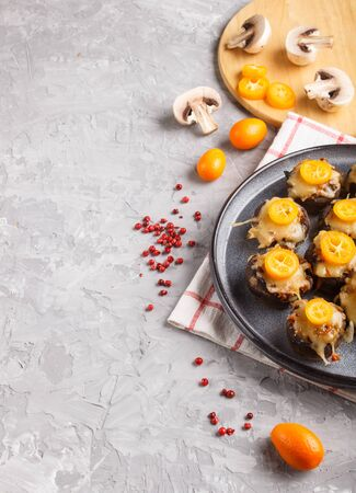 stuffed fried champignons with cheese, kumquats and green peas on a gray concrete background. ceramic plate, side view,  copy space, vertical. Reklamní fotografie