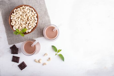 Organic non dairy cashew chocolate milk in glass and wooden plate with cashew nuts on a gray concrete background. Vegan healthy food concept, flat lay, top view, copy space.