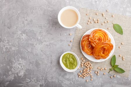 traditional indian candy jalebi in white plate with mint chutney on a gray concrete background. top view, copy space.
