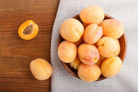 Fresh orange apricots in wooden bowl on wooden background. top view, flat lay, close up. Reklamní fotografie