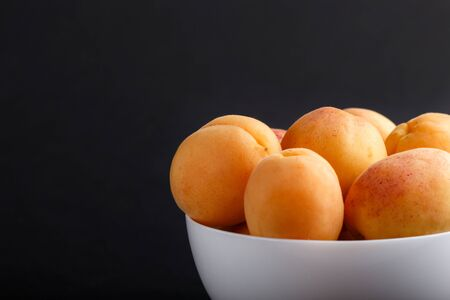 Fresh orange apricots in white bowl on black background. side view, close up, selective focus.