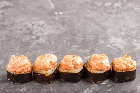 Japanese maki sushi rolls with flying fish roe, cheese on black concrete background. Side view, close up, copy space.