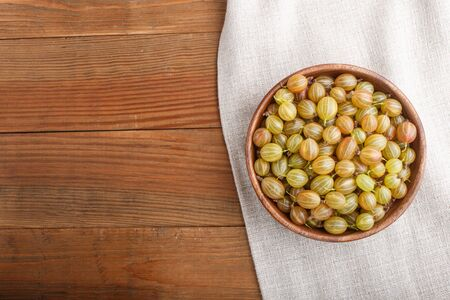 Fresh green gooseberry in wooden bowl on wooden background. top view, flat lay, copy space. Reklamní fotografie