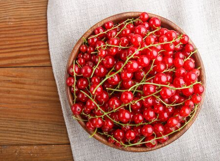 Fresh red currant in wooden bowl on wooden background. top view, flat lay, close up. Reklamní fotografie
