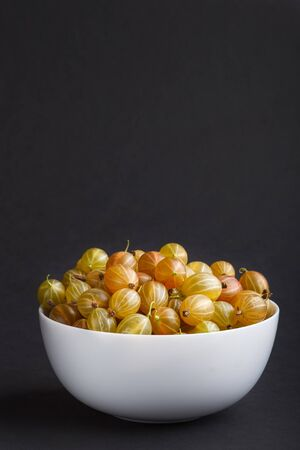 Fresh green gooseberry in white bowl on black background. side view, copy space, close up.