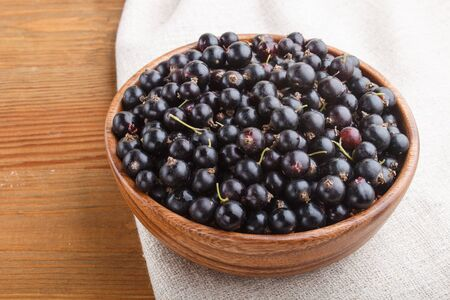 Fresh black currant in wooden bowl on wooden background. side view, close up.