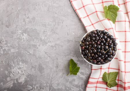 Fresh black currant in white bowl and linen textile on gray concrete background. top view, copy space. Reklamní fotografie