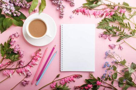 Purple lilac and bleeding heart  flowers and a cup of coffee with notebook and colored pencils on pastel pink background. Morninig, spring, fashion composition. Flat lay, top view.
