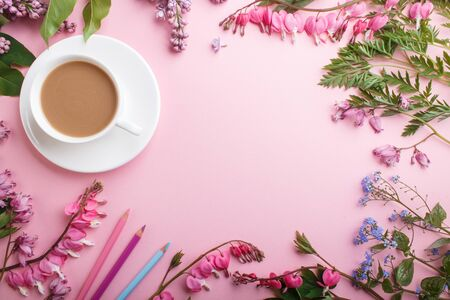 Purple lilac and bleeding heart  flowers and a cup of coffee on pastel pink background. Morninig, spring, fashion composition. Flat lay, top view, copy space. Reklamní fotografie