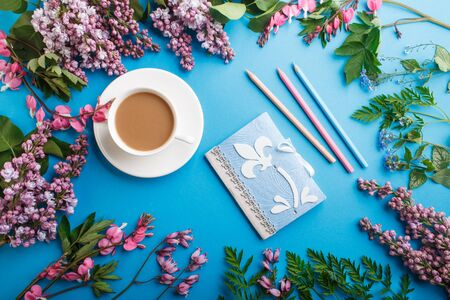 Purple lilac and bleeding heart  flowers and a cup of coffee with notebook and colored pencils on pastel blue background. Morninig, spring, fashion composition. Flat lay, top view.