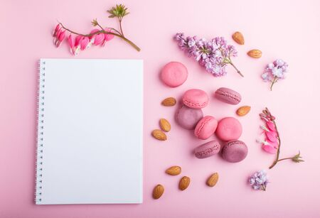 Purple and pink macaron or macaroon cakes with notebook and  lilac and bleeding heart flowers on pastel pink background. Morninig, spring, fashion composition. Flat lay, top view.