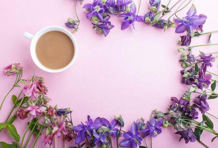 Pink and purple columbine flowers and a cup of coffee on pastel pink background. Morninig, spring, fashion composition. Flat lay, top view, copy space. Reklamní fotografie