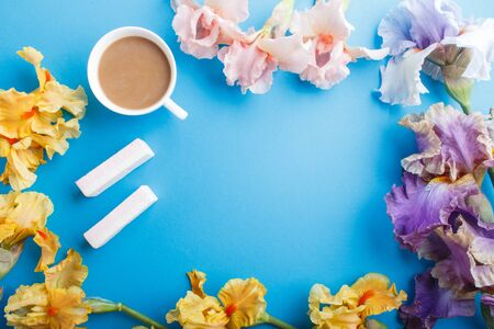 Purple, pink, yellow iris flowers and a cup of coffee on pastel blue background. Morninig, spring, fashion composition. Flat lay, top view, copy space.