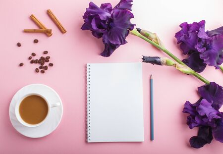 Purple iris flowers and a cup of coffee with notebook on pastel pink background. Morninig, spring, fashion composition. Flat lay, top view, copy space.