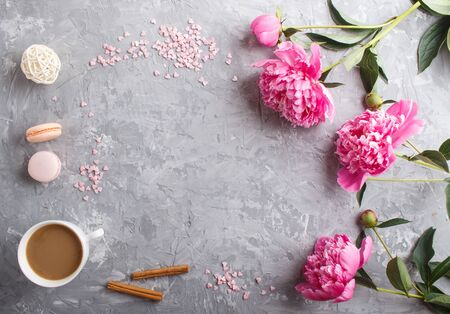Pink peony flowers and a cup of coffee on a gray concrete background. Morninig, spring, fashion composition. Flat lay, top view, copy space. Reklamní fotografie