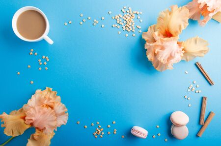Orange iris flowers and a cup of coffee on a blue pastel background. Morninig, spring, fashion composition. Flat lay, top view, copy space.