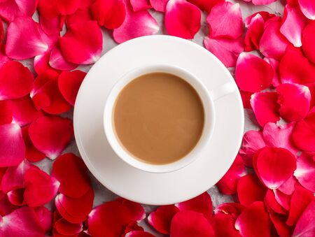 Red rose petals background and a cup of coffee. Morninig, spring, fashion composition. Flat lay, top view, close up. Reklamní fotografie