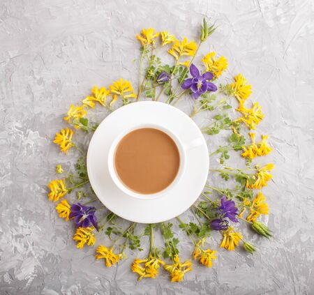 Yellow and blue flowers in a spiral and a cup of coffee on a gray concrete background. Morninig, spring, fashion composition. Flat lay, top view, close up.