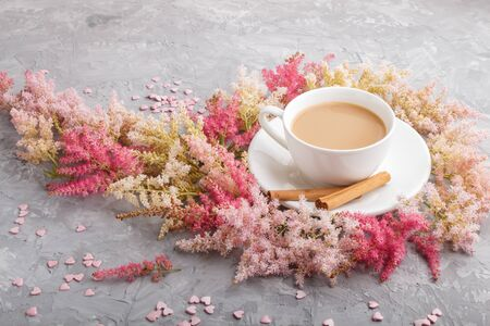Pink and red astilbe flowers and a cup of coffee on a gray concrete background. Morninig, spring, fashion composition. side view, close up.