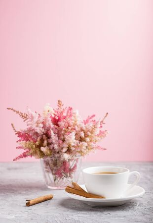 Pink and red astilbe flowers in glass and a cup of coffee on a gray and pink background. Morninig, spring, fashion composition. side view, close up, selective focus. Reklamní fotografie