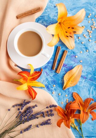 Orange day-lily and lavender flowers and a cup of coffee on a blue concrete background, with orange textile. Morninig, spring, fashion composition. Flat lay, top view, close up.
