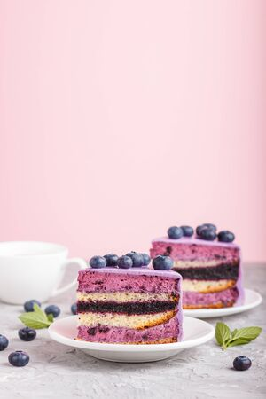 Homemade cake with souffle cream and blueberry jam with cup of coffee and fresh blueberries on gray and pink background. side view, selective focus, copy space. Reklamní fotografie