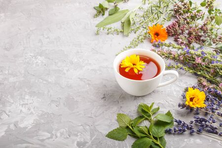 Cup of herbal tea with calendula, lavender, oregano, hyssop, mint and lemon balm on a gray concrete background. Morninig, spring, healthy drink concept. Side view, copy space.