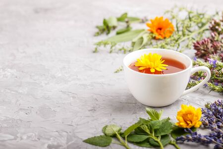 Cup of herbal tea with calendula, lavender, oregano, hyssop, mint and lemon balm on a gray concrete background. Morninig, spring, healthy drink concept. Side view, selective focus, copy space. Reklamní fotografie