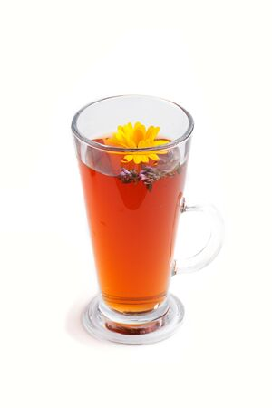 Glass of herbal tea with calendula and hyssop isolated on white background. Morninig, spring, healthy drink concept. Side view, close up.