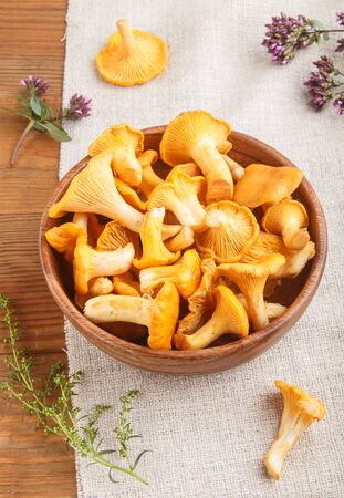 Chanterelle mushrooms in wooden bowl and spice herbs on wooden background with linen textile. side view, close up. Reklamní fotografie
